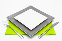 White and gray square plates on the white wooden table.