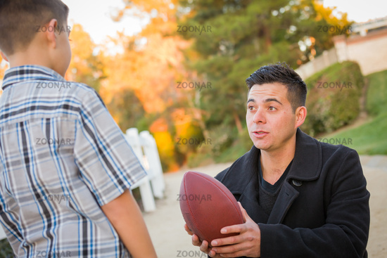 Hispanic Father Holding Football Teaching Young Boy