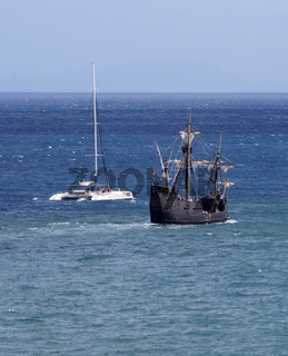 the replica santa maria sailing ship leaving funchal in madeira with a catamaran on a coastal tourist trip