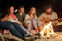 friends roasting marshmallow and playing guitar
