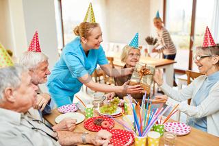Junge Pflegehilfe gibt Seniorin ein Geschenk