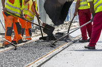 Workers construct asphalt road and railroad lines