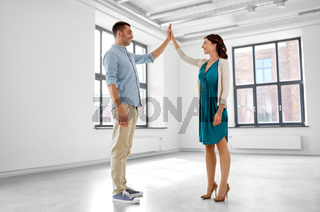 happy couple making high five gesture at new home