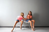 Furious teen girl in a discussion with her little