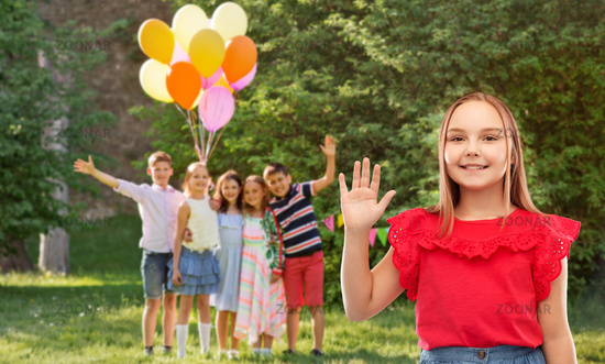 smiling girl waving hand at birthday party in park