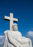 Statue maria with cross and blue sky