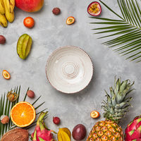 Whole and halves of exotic healthy fruits, carambola, pineapple, passion fruit, pitahaya, palm green leaves and an empty plate on a gray concrete background with space for text. Flat lay
