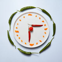 Sliced sweet peppers are laid out on a plate in the form of a clock on a gray background