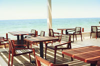 Tables and chairs at outdoor restaurant on the beach