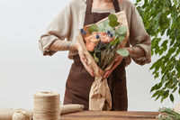 Girl's florist hands hold fresh natural bouquet from fragrant flowers living coral color roses, green leaf in a paper on a background of gray wall, copy space.