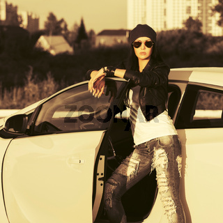 Young fashion hipster woman in sunglasses leaning on her car