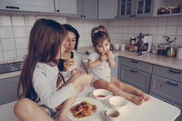 Mom and two daughters eat pancakes