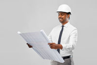 indian male architect in helmet with blueprint