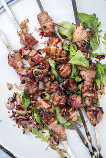Traditional Russian shashlik on a barbecue skewer with roasted onion and lettuce as top view on tray