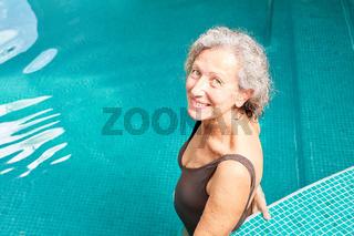 Senior Frau steht entspannt im Schwimmbad