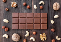 Delicious and sweet milk chocolate on wooden background