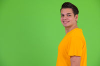 Profile view of happy young multi ethnic man smiling and looking at camera