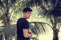 Handosome young man near palm trees