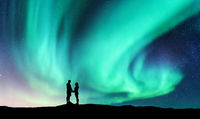 Northern lights and hugging couple on the hill