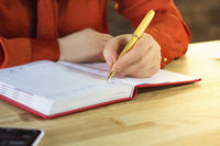 Females hand writing in notebook.