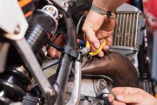 mechanic close up repairing motorbike in repair garage.