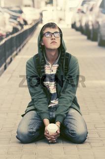 Sad teen boy in depression sitting on sidewalk in city street