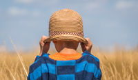 Boy with a straw hat in a countryside
