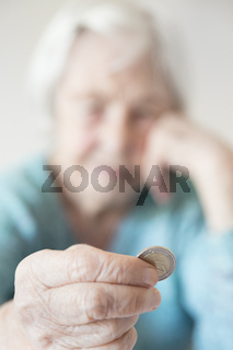Sad elderly woman sitting at the table at home and looking miserably at only remaining coin from pension in her hand.