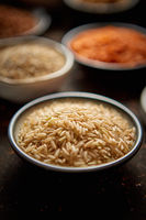 Raw jasmine rice seeds in ceramic bowl. Selective focus