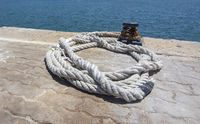 Thick white mooring rope closeup on empty mooring place