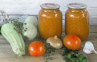 Canned squash caviar with vegetables in glass jars.