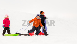 happy little kids with sleds in winter