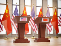 Flags of the USA and China and tribunes at international meeting or conference. Relationship between China and USA concept.