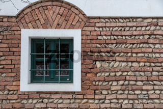 Fenster mit Fenstergitter inmitten einer Ziegelmauer aus Backsteinen und Flusssteinen