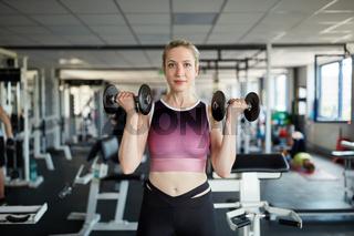 Junge Frau beim Bizeps Training mit Kurzhanteln