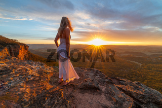 Woman watching blissful sunsets from hidden cliff ledges