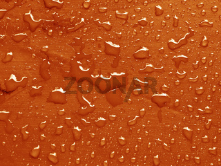 water drops on russet orange colored  metallic surface