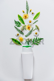 White bottle with cosmetic on white background with field flowers and leaves. The concept of summer and idea for advertisement of liquid soap, cream or shampoo. Flatlay.