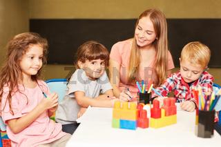Kinder Gruppe und Erzieherin malen zusammen