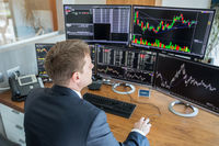 Stock trader looking at computer screens in trdading office.