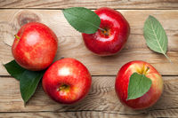 Red Apples with Green Leaves on Wooden Table