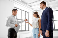 realtor giving key to customers at new office