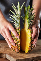 Two halves of ripe organic pineapple hold the girl's hands on an old wooden board. Exotic fruit