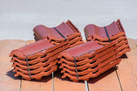Piles of new roof tiles lying on scaffold boards