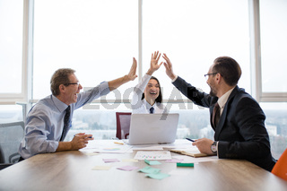 A group of business colleagues giving each other high-five and smiling while working in the officce