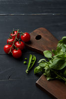 Board with fresh basil, tomatoes and green beans on wooden background
