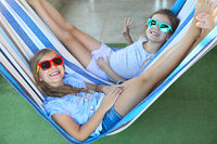 Little happy girls playing on hammock in summer day
