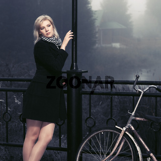 Young fashion woman in black coat in a fog outdoor