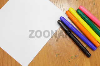 A set of colored markers and a sheet of white paper on the table.