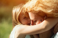 Close-up portrait of little daughter hugging her disabled mother